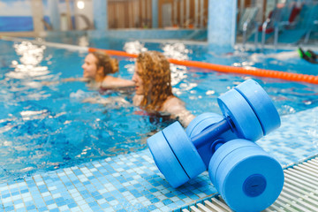 Two happy girls exercising in swimming pool with dumbbells. aqua aerobics classes concept
