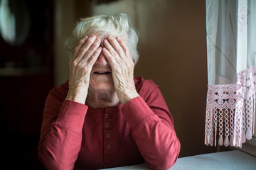 Elderly woman covers face with wrinkled hands.