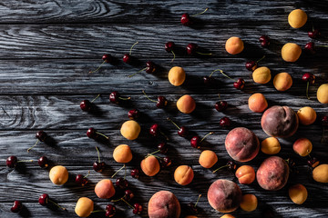 top view of pile of cherries, apricots and peaches on wooden table