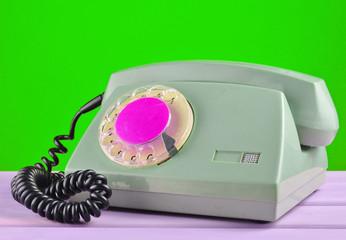 Retro telephone on green background.