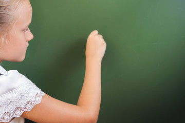 Schoolgirl writes on blackboard with chalk, Back to school