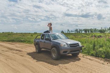 girl on an SUV in a field on a sandy road