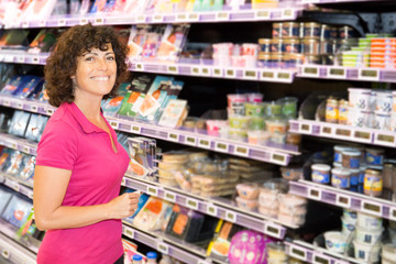 woman looking at some products on a supermarket aisle