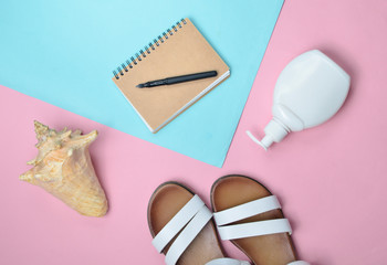 Fashionable leather women's sandals, seashells, sunblock, notepad on colored pastel background, top view, flat lay.