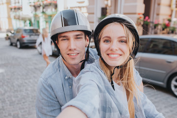 Beautiful couple is sitting on motorcycle's seats and looking on camera. Girl is holding camera. She is taking selfie. They are smiling.