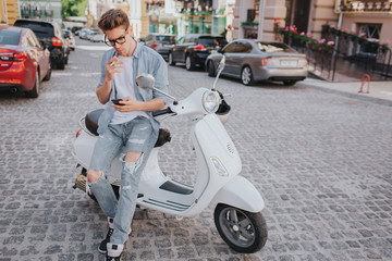 Handsome guy is sitting on motorcycle and holding phone in hand. He is looking at it. Theere is a cigarette in other hand. He is smoking.