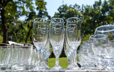 Empty glasses on table outdoors, selective focus, free space. Set of sparkling glassware with, close up. Crystal glasses ready for celebration on table. Wineglasses at luxury wedding reception