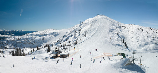 Top of a mountain covered with snow, ski facilities and skiers, Italy