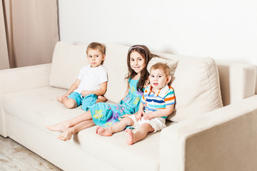 Sister and her two younger brothers in the living room.