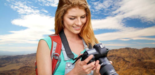 travel, tourism and photography concept - happy young woman with backpack and camera photographing over grand canyon national park hills background