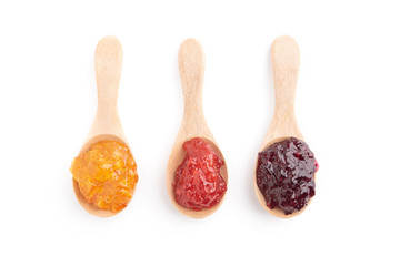 Strawberry, orange and blueberries jam with wooden spoon on a white background. top view.