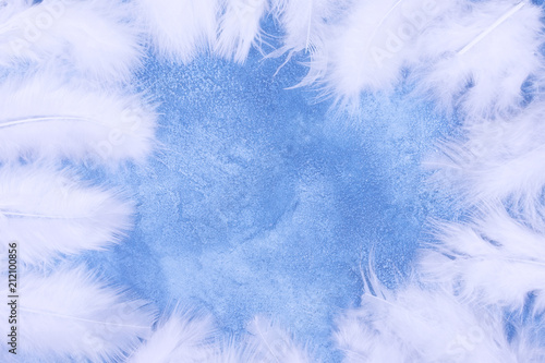 Fluffy White Feathers Forming A Frame On A Light Blue Marble Or