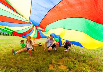 Happy kids hiding under colorful parachute