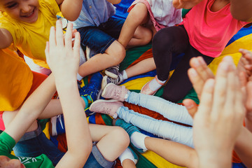 Mass of children's legs on a colorful floor