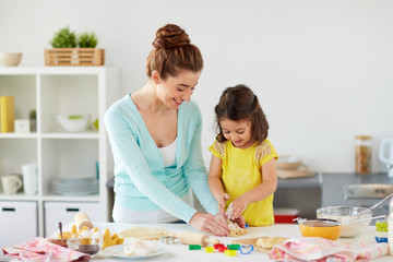 family, cooking and people concept - happy mother and little daughter with molds making cookies from dough at home kitchen