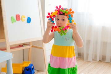 A 3 year old child plays at a table with colorful toy blocks. Children play with educational toys in the kindergarten or room. Preschoolers gather at the table the puzzle out of plastic blocks.