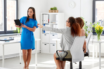 business, technology and people concept - businesswoman showing tablet pc computer to female team at office