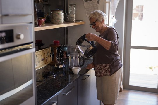 Smiling senior woman pouring water in coffeemaker