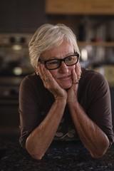 Thoughtful senior woman in kitchen