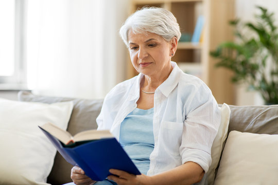 age, leisure and people concept - senior woman reading book at home