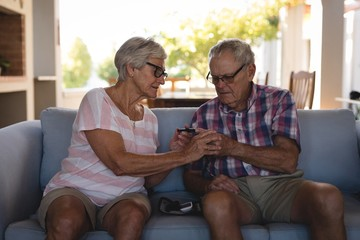 Senior couple checking blood sugar with glucometer in living