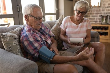 Senior couple checking blood pressure at home