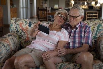 Senior couple taking selfie with mobile phone in living room
