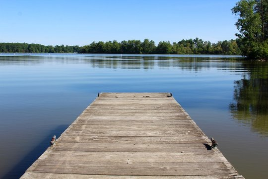 The small wood dock and the reflection lake of the park.