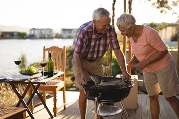 Senior couple cooking fish on barbeque