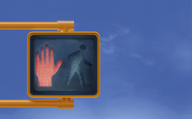Don't  walk red hand stop street signal for pedestrians on blue shy