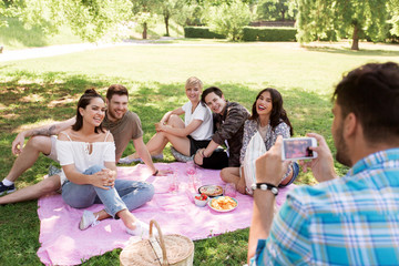 friendship, leisure and technology concept - man taking picture of his friends by smartphone on picnic at summer park