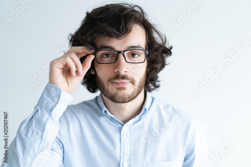 352072e1220 Serious young dark-haired man adjusting glasses. Attractive guy looking at  camera. Smart man concept. Isolated front view on white background.