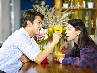 playful young asian couple in coffee shop