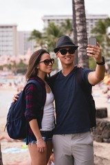 Couple taking selfie with mobile phone near beach
