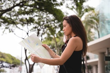 Woman looking at map in city street