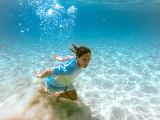 Man swimming under water at sea bottom
