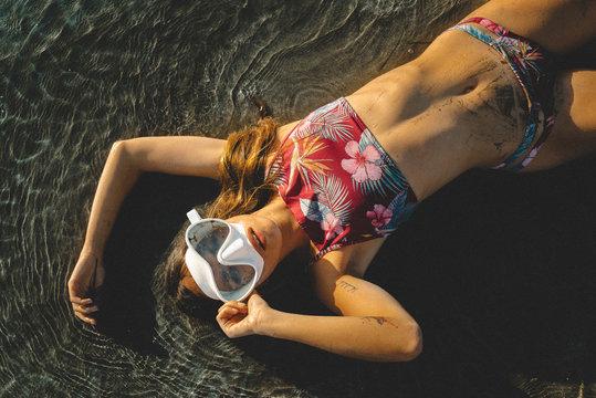 Woman in swimwear lying on sandbank