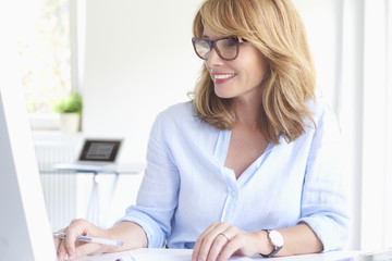 Happy mature businesswoman using computer