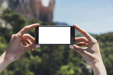 Hipster blogger girl holds mobile phone in female hands, take photo picture of natural landscape on a sunny summer day while travel and vacation, clean blank screen cellphone