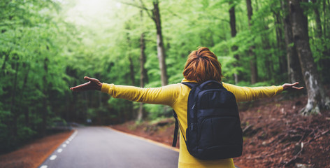 Wall Mural - tourist traveler with backpack standing with raised hands, girl hiker view from back looking into road at forest with arms outstretched and enjoying fresh air in trip, relax holiday concept
