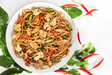 traditional spicy asian cuisine food: wok stir fry spaghetti with fried chicken and thai spices and herbs