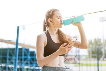 beautiful girl in sports uniform, doing exercises on the street, running around, drinking water and listens to music on the phone. Healthy way of life, an infused figure