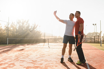 Tennis players taking selfie after match in the morning sunlight