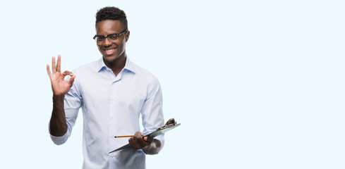 Young african american man holding a clipboarad doing ok sign with fingers, excellent symbol