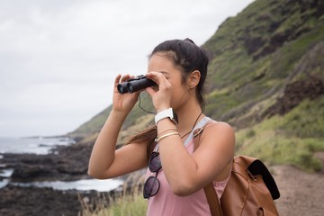 Woman looking through binoculars in countryside