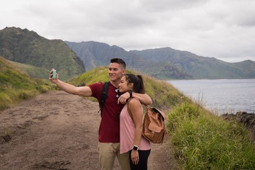 Couple taking selfie with mobile phone in countryside
