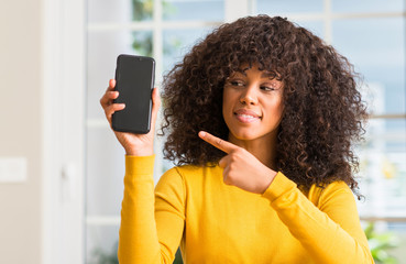 African american woman using smartphone very happy pointing with hand and finger