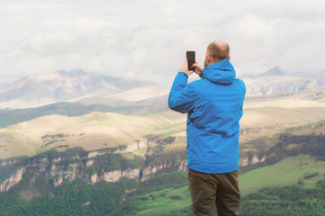 A bearded man in a membrane blue jacket stands in the nature against the backdrop of the mountains and takes pictures on the telephone landscape