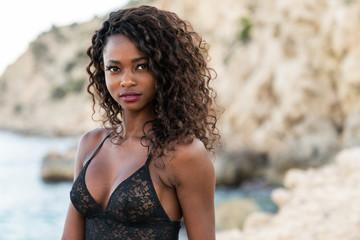 Beautiful black woman on fence above sea