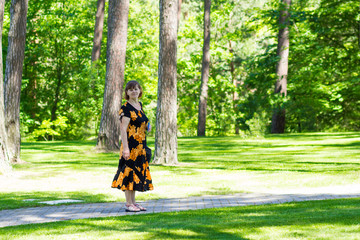 Happy senior woman walk in beautiful summer garden and breathes fresh air. Harmony with nature